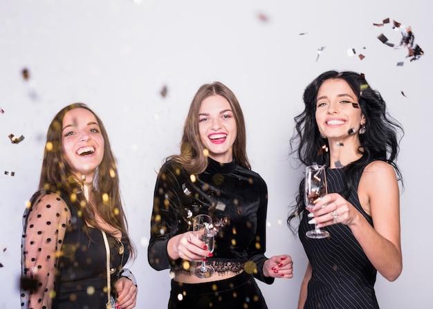 Heureuse femme debout avec des coupes à champagne sous les paillettes Photo gratuit