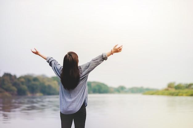 Heureuse femme debout près de la rivière. levant les bras pour respirer l'air frais Photo Premium