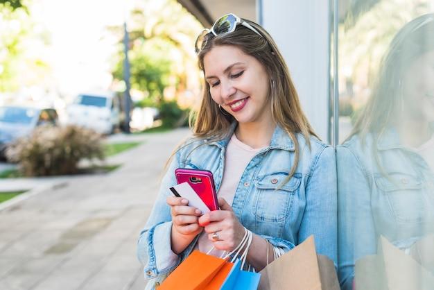 Heureuse femme debout avec des sacs à provisions, smartphone et carte de crédit à l'extérieur Photo gratuit