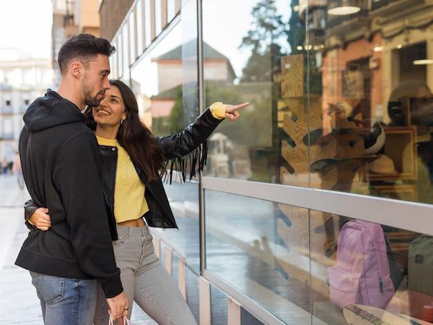 Heureuse femme étreignant et montrant sur la vitrine d'un jeune homme Photo gratuit