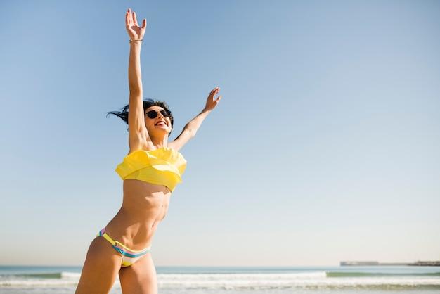 Heureuse femme excitée en bikini jaune, levant leurs mains à la plage contre le ciel bleu clair Photo gratuit