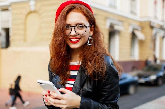 Heureuse Femme Gingembre Fabuleux En élégant Béret Rouge Dans La Rue à L'aide De Smartphone Photo gratuit