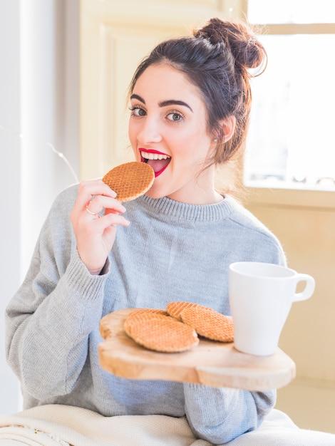 Heureuse femme en gris mangeant des biscuits Photo gratuit