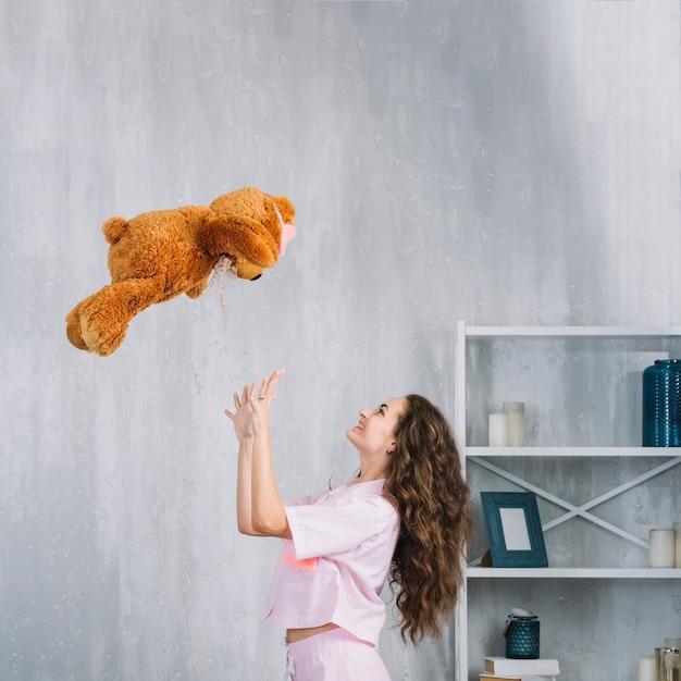 Heureuse Femme Jetant Une Peluche Dans Les Airs à La Maison Photo gratuit