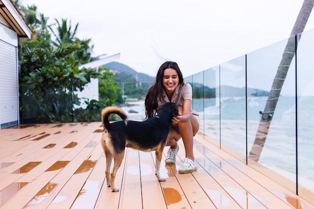 Heureuse Femme Jouant Avec Un Chien En Terrasse Avec Paysage Marin Photo gratuit