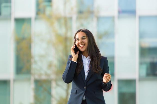 Heureuse femme latine parle sur téléphone portable Photo gratuit