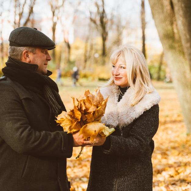Heureuse femme mature blonde et bel homme brune d'âge moyen à pied dans le parc, se regardant Photo Premium