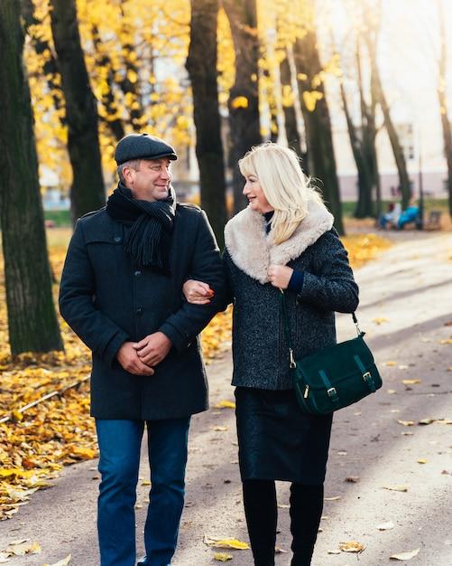 Heureuse Femme Mature Blonde Et Bel Homme Brune D'âge Moyen à Pied Dans Le Parc Photo Premium