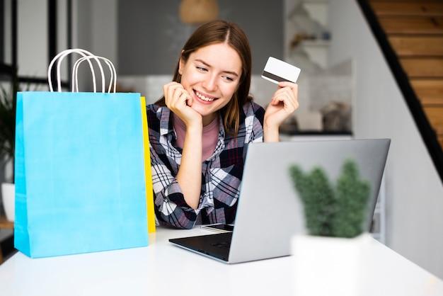 Heureuse femme montrant une carte de crédit et regardant un ordinateur portable Photo gratuit