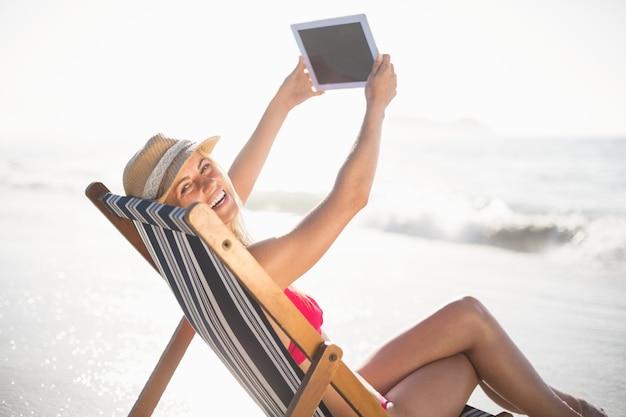 Heureuse femme parlant un selfie sur une tablette numérique Photo Premium