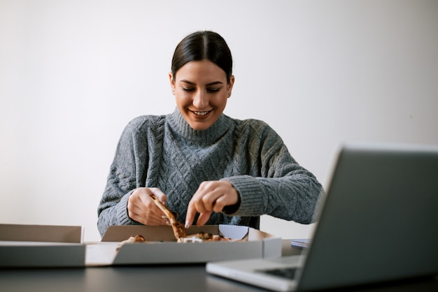 Heureuse femme prenant une pointe de pizza en position assise devant un ordinateur portable. Photo Premium