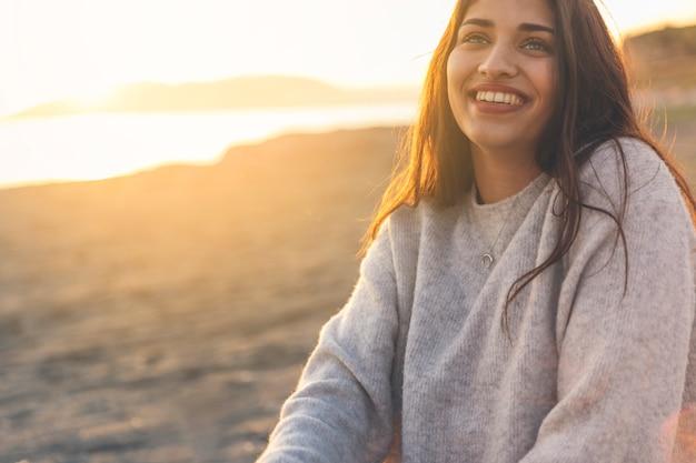 Heureuse femme en pull assis sur le bord de mer de sable Photo gratuit
