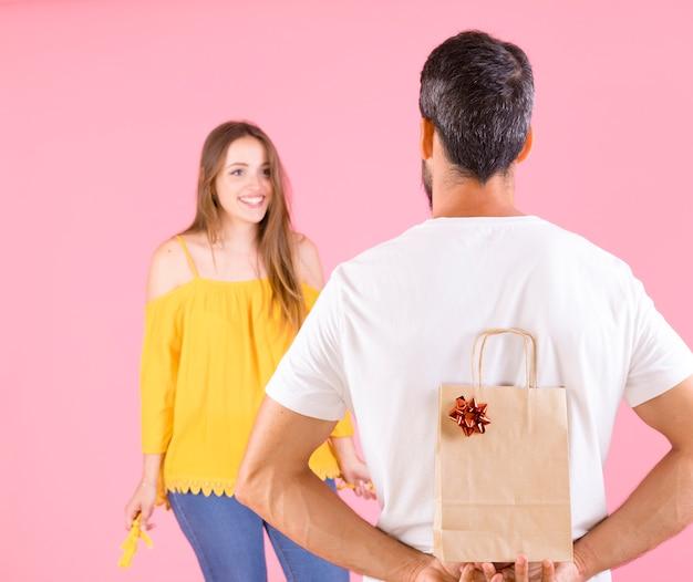Heureuse femme regardant son petit ami tenant des boîtes-cadeaux sur fond rose Photo gratuit
