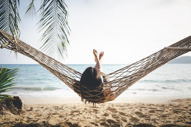 Heureuse femme relaxante dans un hamac Photo Premium
