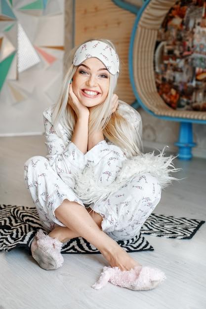 Heureuse femme rit et s'assoit en pyjama par terre. masque de sommeil. Photo Premium