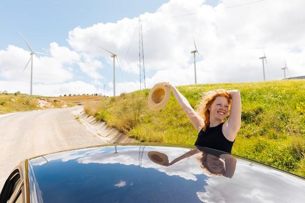 Heureuse femme rousse sur une route secondaire Photo gratuit
