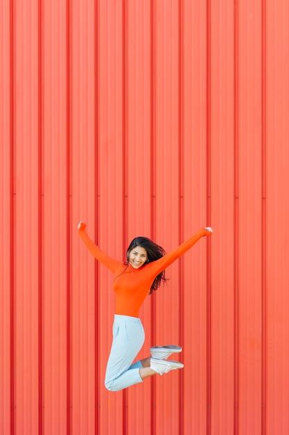 Heureuse femme sautant sur un fond ondulé rouge tandis que le bras tendu Photo gratuit
