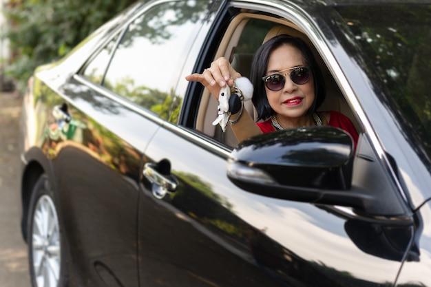 Heureuse femme senior au volant et montrant sa nouvelle clé de voiture. Photo Premium