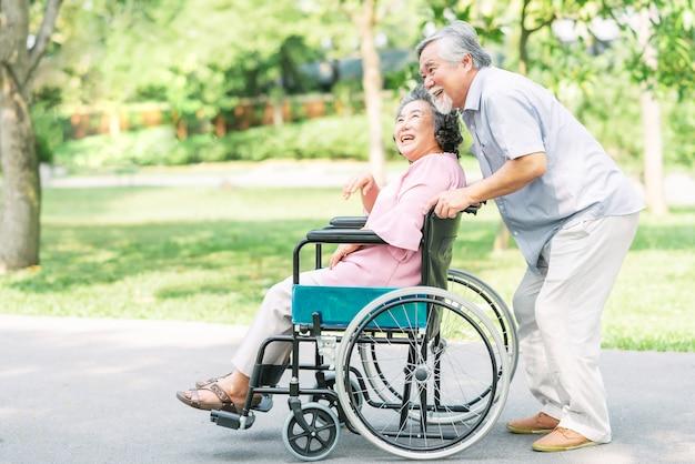 Heureuse femme senior en fauteuil roulant avec son mari Photo Premium