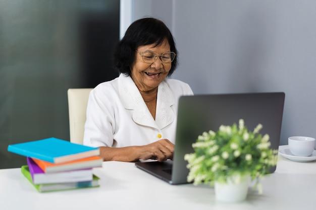 Heureuse Femme Senior Travaillant Sur Ordinateur Portable Photo Premium
