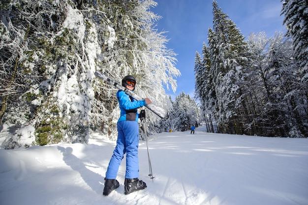 Heureuse femme skieur sur une piste de ski dans la forêt Photo Premium