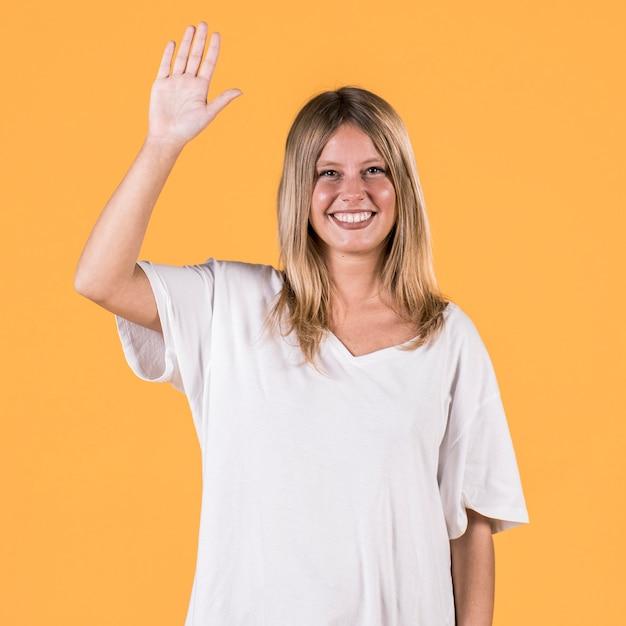 Heureuse femme sourde avec bras levé debout devant le fond uni Photo gratuit