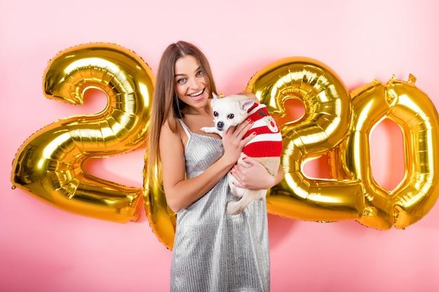 Heureuse Femme Souriante Avec Chien Blanc Chihuahua Et Ballons De Noël 2020 Isolés Sur Rose Photo Premium