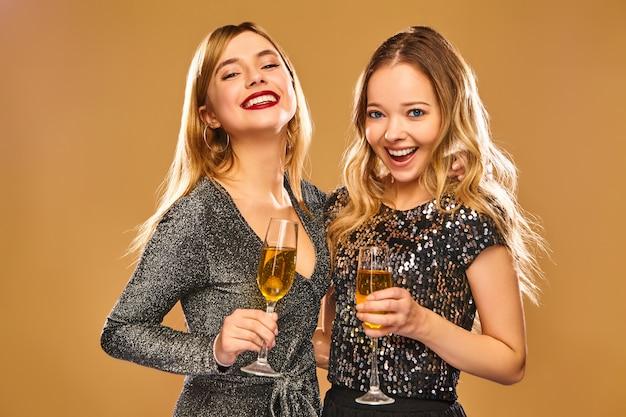 Heureuse Femme Souriante Dans Des Robes Glamour élégantes Avec Des Verres De Champagne Photo gratuit