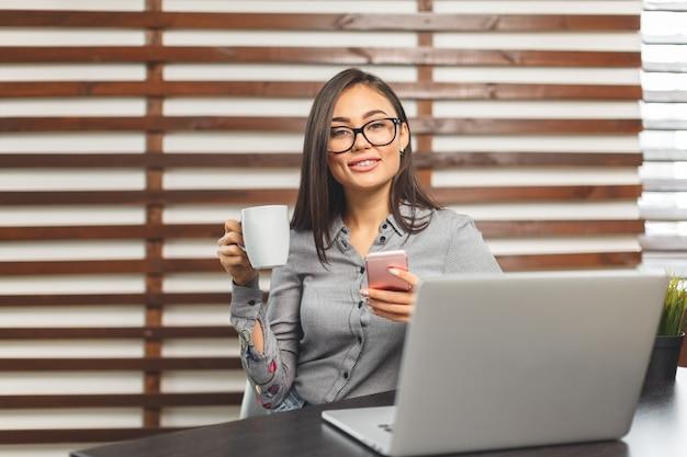 Heureuse femme souriante travaillant avec un ordinateur portable et de boire du café Photo Premium