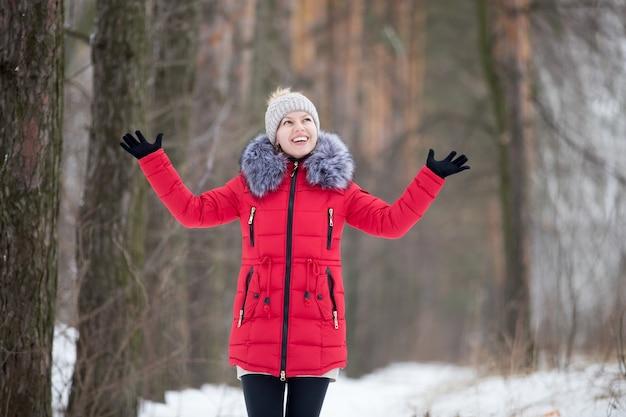 Heureuse femme souriante en veste d'hiver rouge, en plein air Photo gratuit