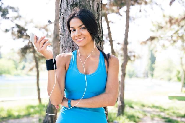 Heureuse Femme Sportive Tenant Le Smartphone à L'extérieur Photo Premium