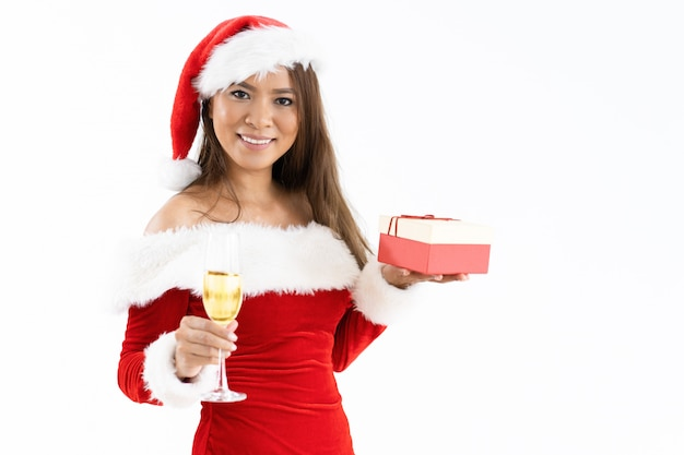 Heureuse femme tenant une boîte-cadeau de noël et un verre à champagne Photo gratuit