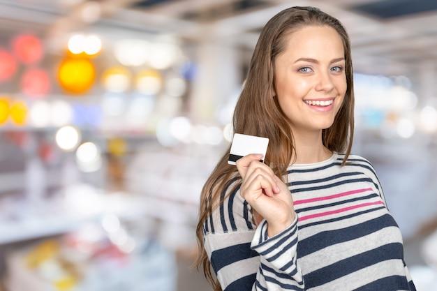 Heureuse femme tenant une carte de crédit Photo Premium