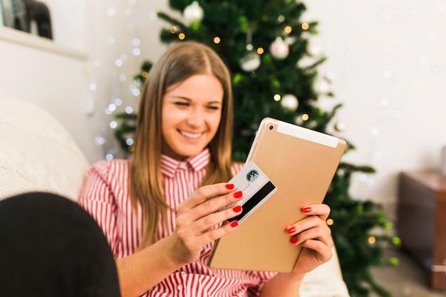 Heureuse femme tenant une tablette et une carte de crédit près d'un arbre de noël Photo gratuit