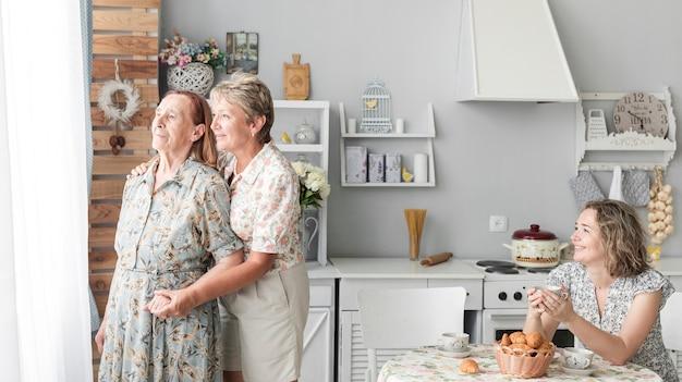Heureuse femme tenant une tasse de café en regardant sa mère et grand Photo gratuit