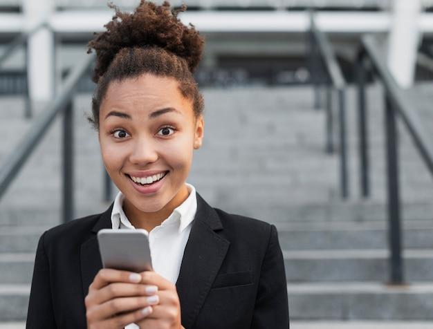 Heureuse femme tenant un téléphone Photo gratuit