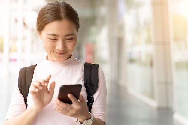 Heureuse femme utilisant un téléphone intelligent dans la ville Photo Premium