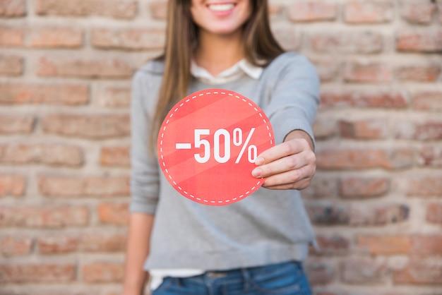 Heureuse femme en vêtements décontractés avec signe Photo gratuit