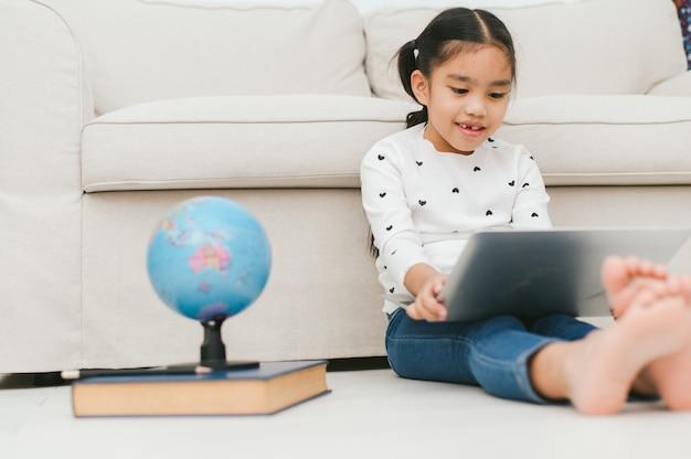 Heureuse fille asiatique à l'aide d'un ordinateur portable Photo Premium