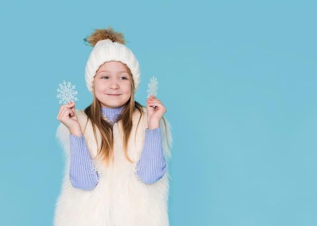 Heureuse fille jouant avec des flocons de neige Photo gratuit