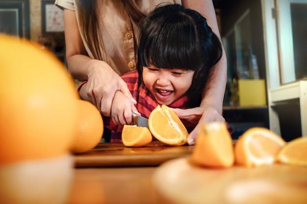 Heureuse Fille Mignonne De 3-4 Ans Avec Sa Mère Tranche Un Peu D'orange Sur Une Table En Bois Dans La Salle Pantry Photo Premium