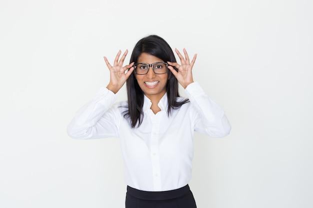 Heureuse fille positive de bureau mettant des lunettes Photo gratuit