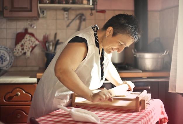 Heureuse grand-mère faisant des pâtes Photo Premium
