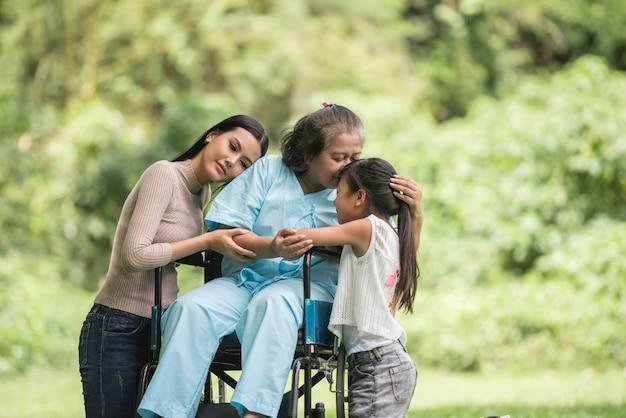 Heureuse grand-mère en fauteuil roulant avec sa fille et son petit-fils dans un parc, happy life happy time. Photo gratuit