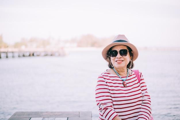 Heureuse Haute Femme Asiatique Assise à L'extérieur Photo Premium