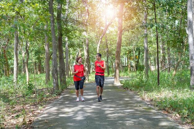 Heureuse haute femme asiatique avec homme ou entraîneur personnel jogging en cours d'exécution dans le parc Photo Premium