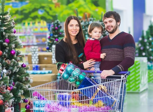 Heureuse jeune famille au supermarché choisit des cadeaux pour la nouvelle année. Photo Premium