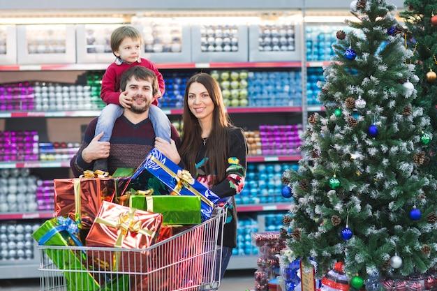 Heureuse Jeune Famille Dans Le Supermarché Choisit Des Cadeaux Pour Noël Photo Premium
