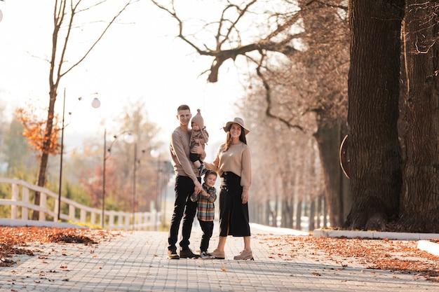 Heureuse Jeune Famille Avec Deux Petits Enfants Marchant Et S'amusant Dans Le Parc D'automne Aux Beaux Jours Photo Premium
