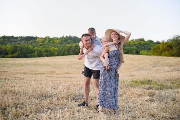 Heureuse jeune famille. un père, une mère enceinte et deux petits fils sur le dos. champ de blé biseauté. coucher du soleil Photo Premium